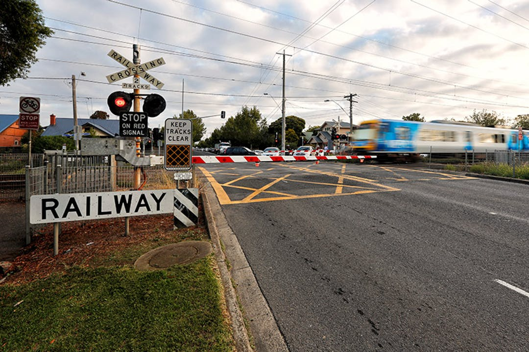 Train traveling through a level crossing at Grange Road in Alphington with the boom gate down