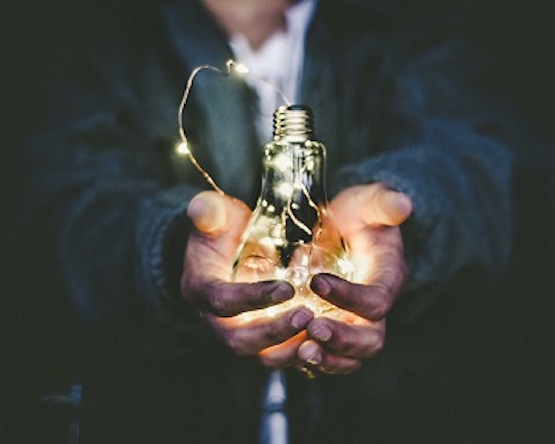 An image of a person holding a light bulb in their hands