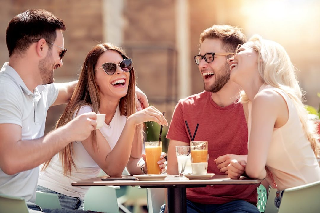 Four friends at a cafe table outside