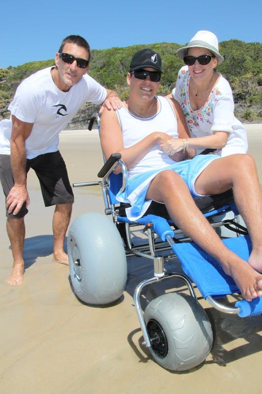 Cabarita Beach resident Sam Ford and his parents, Michael and Margaret, with the new beach wheelchair provided by Council and the Cabarita Beach Surf Lifesaving Club.