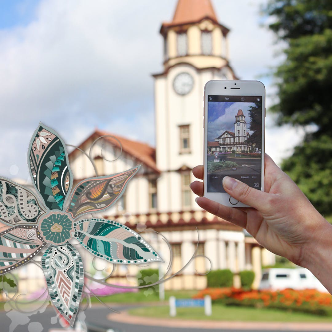Photo of someone taking a photo of the clock tower at the iSite centre in Rotorua
