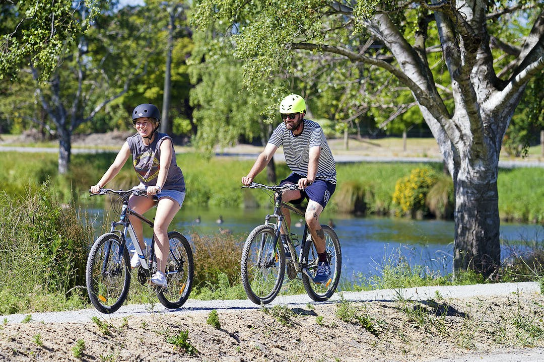 This image shows two people cycling alongside the Ōtākaro Avon River.