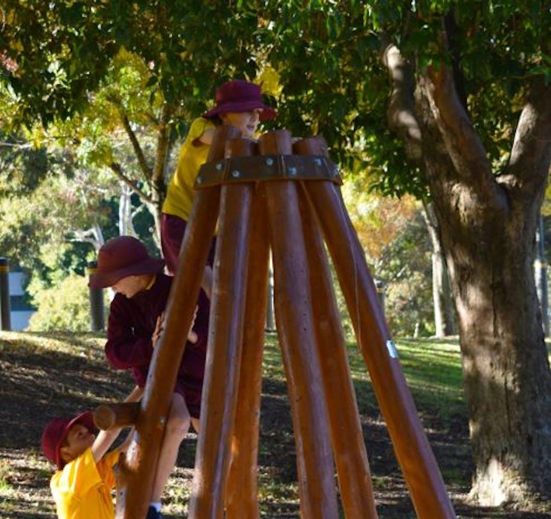 Kids climbing tepee.