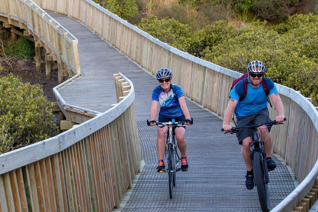 Two people taking part in a bike ride on a cycle path.
