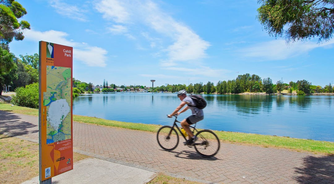 Image of man cycling on a path in front of water.