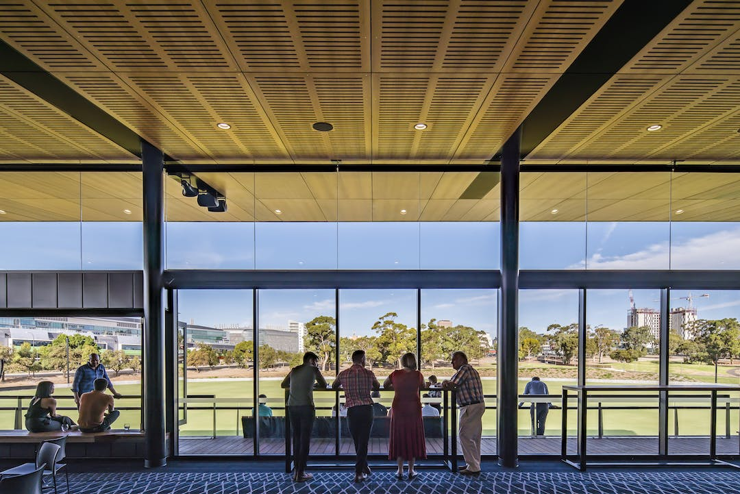 Photo of people chatting inside a building and looking out through the floor to ceiling windows to park lands and a blue sky.