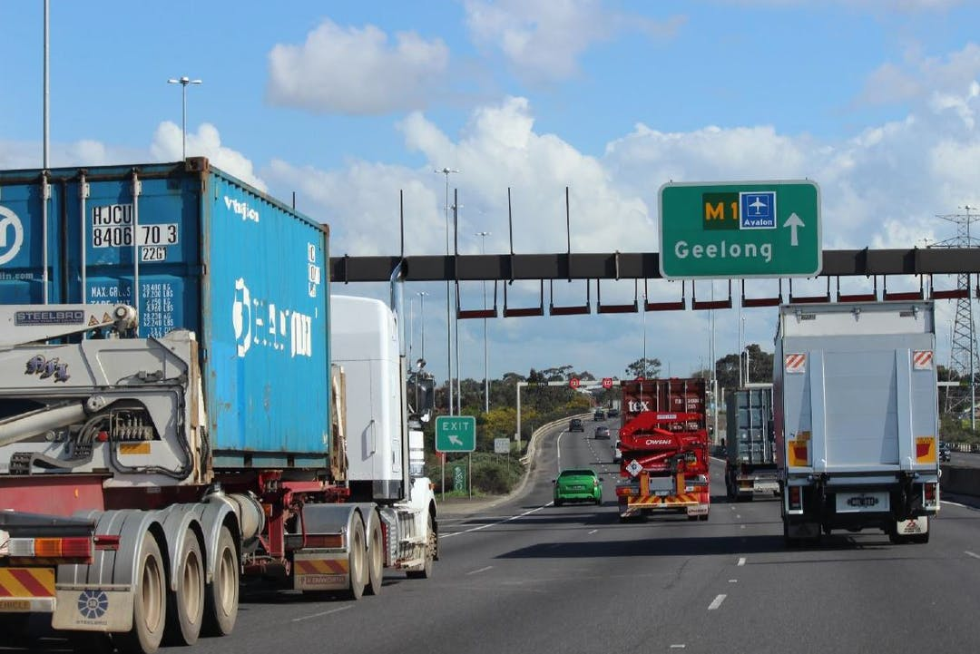 Container trucks and cars on M1 freeway heading towards Wet Gate Bridge and Geelong