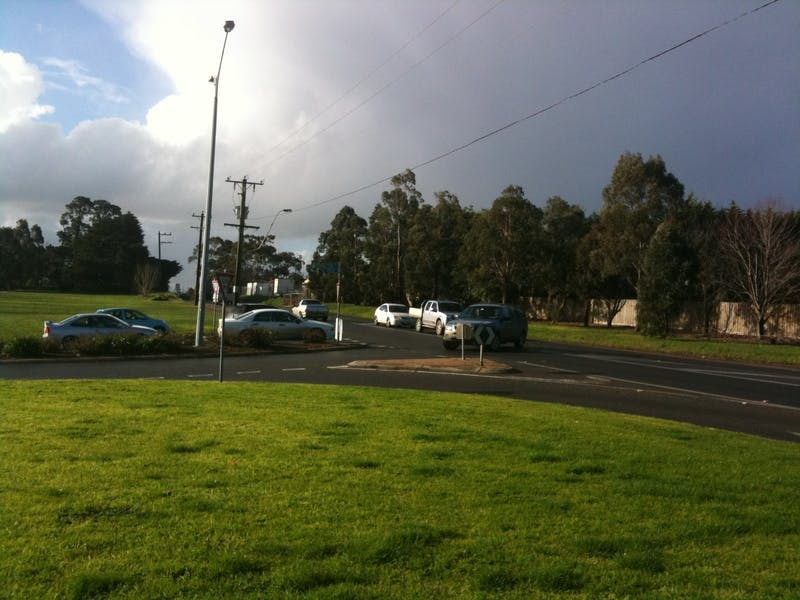 Commuters wait at the intersection of Narre Warren-Cranbourne Road and Baringa Park Drive
