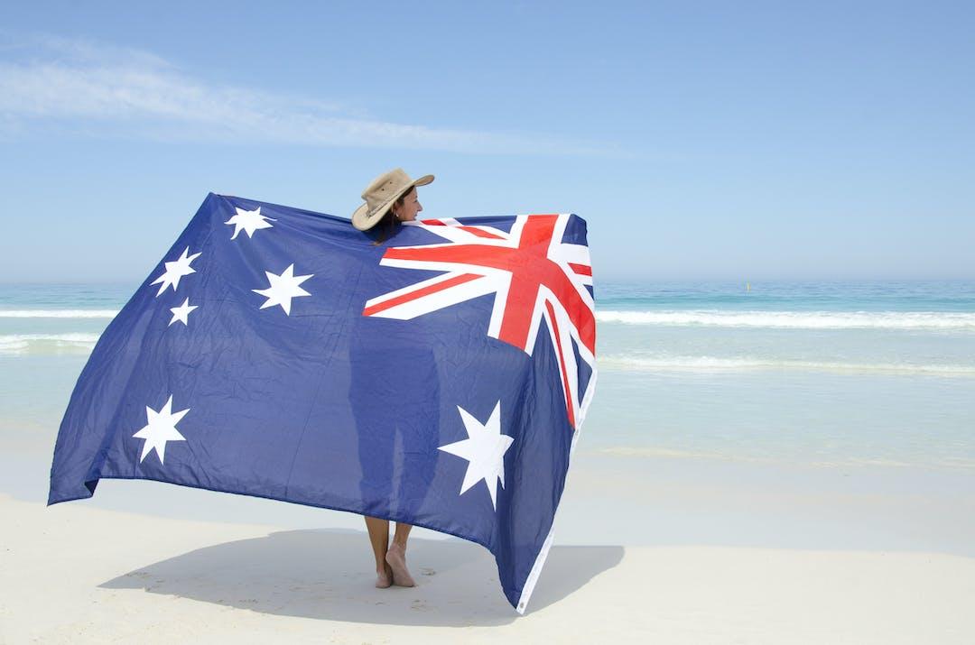Australian flag woman holding flag on beach
