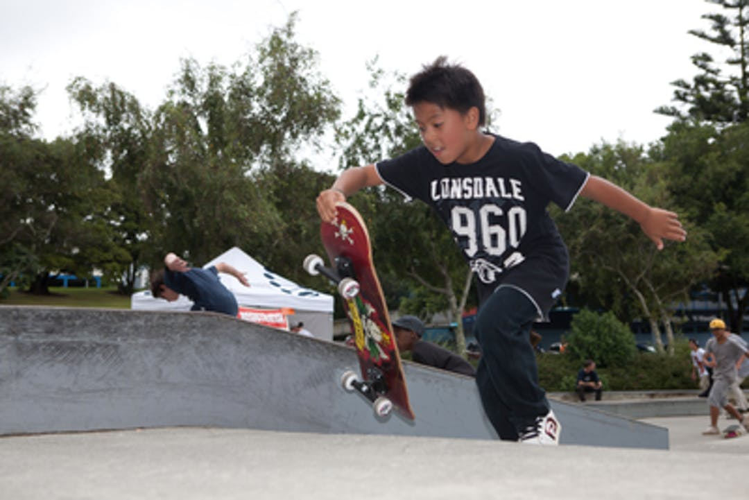 A child doing a skateboard trick in a skate park