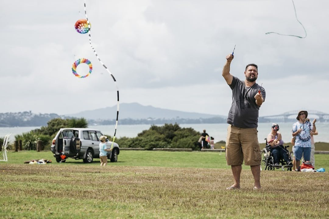 Man in foreground flying a kite with people in background and Rangitoto in the distance