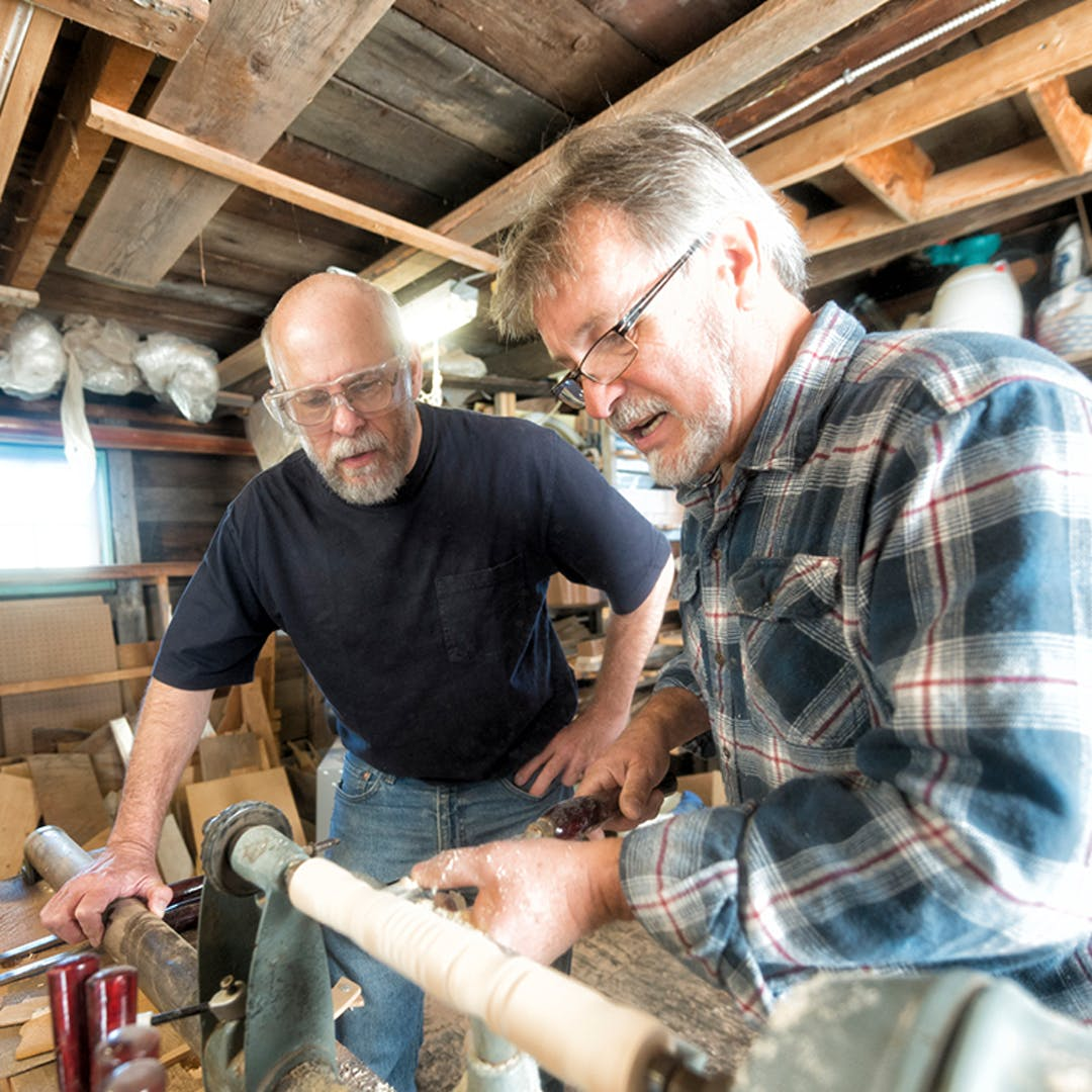 Two men doing woodwork in a shed