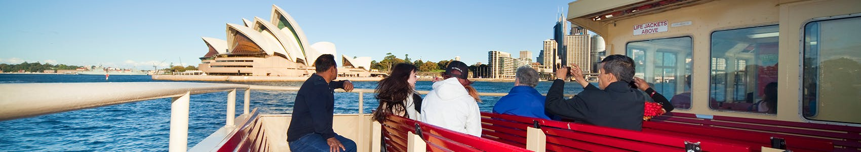 Image a passengers on a ferry with Sydney's skyline in the background