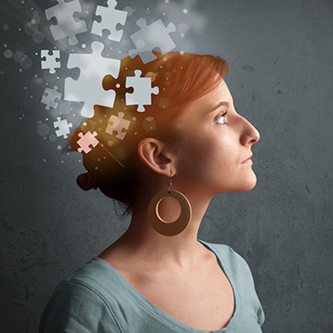Image of woman looking out of frame with jigsaw puzzle pieces flowing from her hear (mental health image)